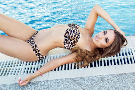bikini sexy: Sexy fashion smiling woman is wearing leopard printed bikini with tanned skin is lying near swimming pool on blue deck chair, summer time