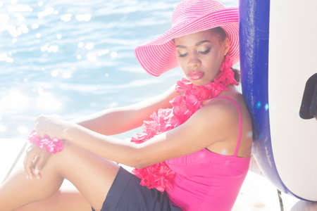 pink hat: Young south african zulu woman is wearing pink hat and hawaiian flowers is sitting near the sea Stock Photo