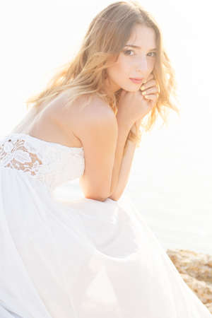 summer dress: Beautiful young bride girl is sitting on rock at sunset time