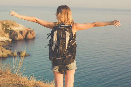 Back view traveler girl is standing on rock edge with backpack over sea view with backpack, summer time