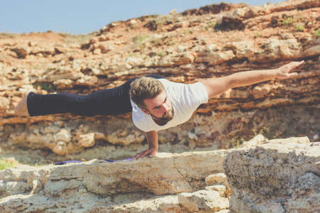 spirituality therapy: Young sportive man is practicing acroyoga exercises in the early morning on the beach with stones Stock Photo