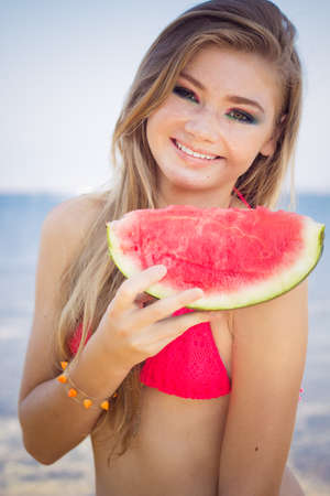 Beauty smiling teenager girl is wearing pink bikini and eating watermelon near sea