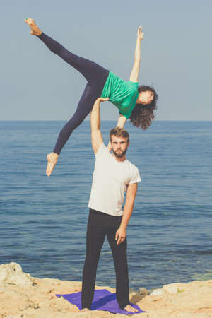 trust people: Couple are practicing acroyoga exercises in the early morning on the sea coast Stock Photo