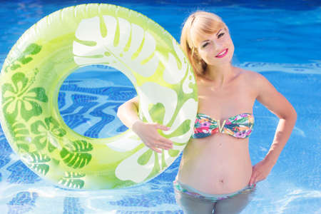 rubber ring: Beautiful pregnant woman is holding green rubber ring in blue water of swimming pool, summer vacations