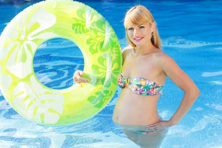 water aerobics: Beautiful pregnant woman is holding green rubber ring in blue water of swimming pool, water aerobics