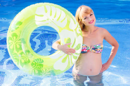 water aerobics: Beautiful smiling pregnant woman is holding green rubber ring in blue water of swimming pool, water aerobics