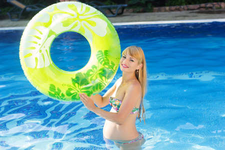 rubber ring: Beautiful smiling pregnant woman is holding green rubber ring in blue water of swimming pool, water aerobics