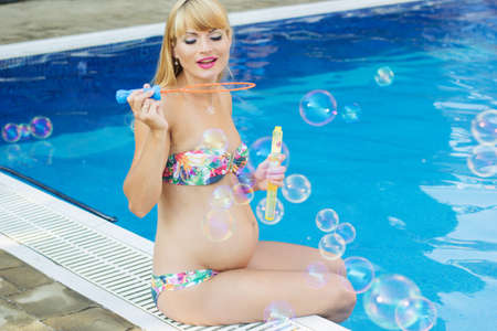 pink bikini: Beautiful pregnant blonde woman is making soap bubbles near swimming pool with blue water, vacations