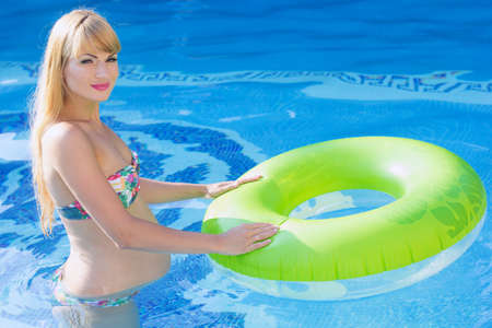 rubber ring: Beautiful smiling pregnant woman is holding green rubber ring in swimming pool, water aerobics