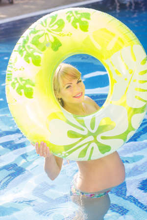 water aerobics: Beautiful smiling happy pregnant woman is holding green rubber ring in swimming pool, water aerobics