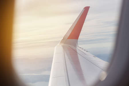 airplane: View of wing of an airplane flying above the clouds, morning time Stock Photo