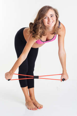 Happy pregnant woman doing stratching exercises with special sports rubber band isolated on white in studio