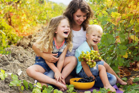 happy family nature: A cute happy family mother and two happy childrens boy and girl outdoor are holding bunch of grapes in autumn vineyard Stock Photo