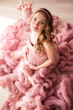 7f722e3ef  77035332 - La muchacha bonita embarazada está llevando el vestido rosado  de la moda