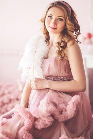f1445c7ea  77243877 - La muchacha bonita embarazada está llevando el vestido rosado  de la moda