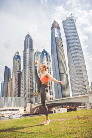 asana: Young girl doing stretching against skyscrapers