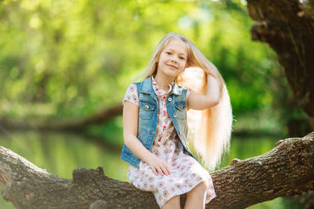 Cute little girl sitting on log under river Stock Photo
