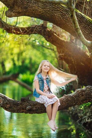 Beautiful little girl sitting on log under river