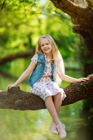 Beautiful child girl sitting on log under river outdoors