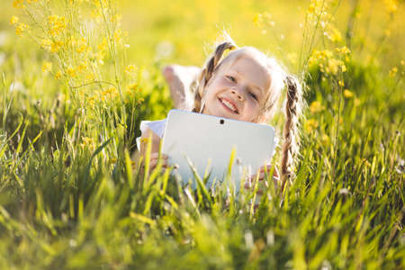 technoligy: Little blonde girl with digital tablet on the nature Stock Photo