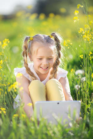 technoligy: Little blonde girl with digital tablet in yellow field Stock Photo