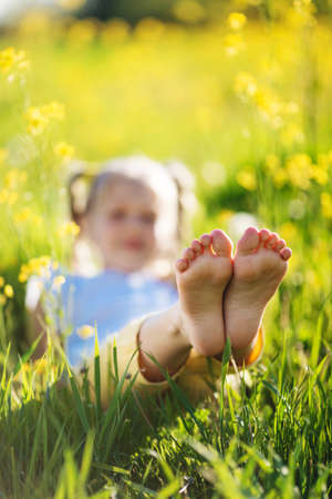 Feet of little girl in yellow field with flowers