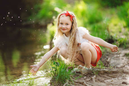 Beautiful little girl having fun near river
