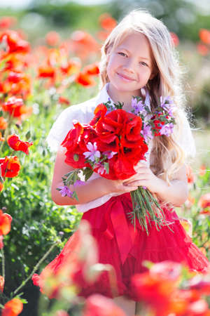 Cute blonde child girl with bouquet of poppies Stock Photo