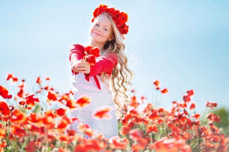 Cute blonde child girl in poppy field