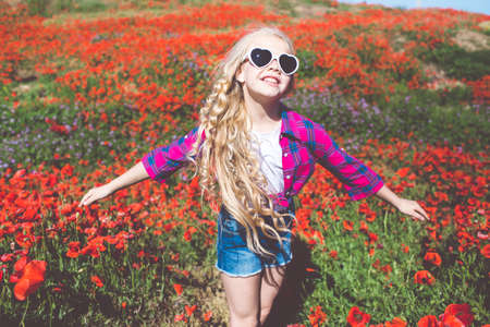 Child girl is wearing sunglasses and casual clothes in spring field with bouquet of poppies
