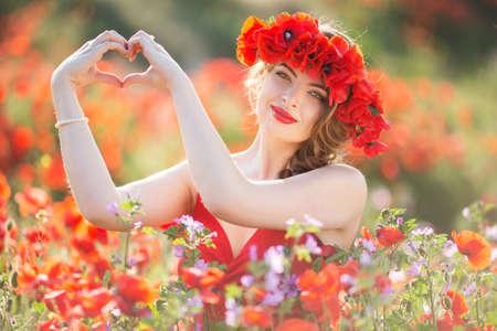 Mujer de moda en el campo de flores de amapola roja, el tiempo de primavera