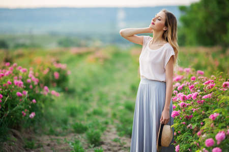 Beautiful young girl is wearing casual clothes sitting in a garden with pink blossom roses Stock Photo