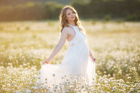 Beautiful happy pregnant girl on the field of daisy flowers in sunset lights Stock Photo