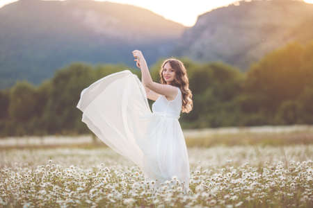 Beautiful happy pregnant girl on the field of daisy flowers Stock Photo