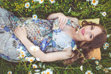 drowsy: Beautiful pregnant smiling woman lying in the camomile field