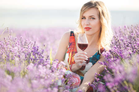 Beautiful blonde sexy woman is drinking red dry wine in lavender field Stock Photo