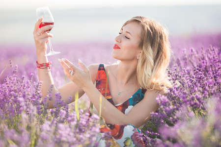 Beautiful blonde sexy woman is drinking red wine in lavender field Stock Photo
