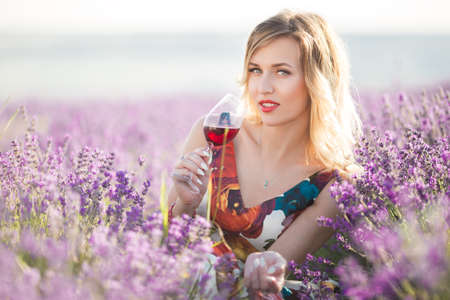 Portrait of beautiful sexy girl is drinking red wine in lavender field
