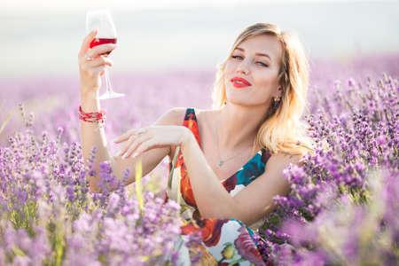 Portrait of beautiful sexy girl is drinking wine in lavender field