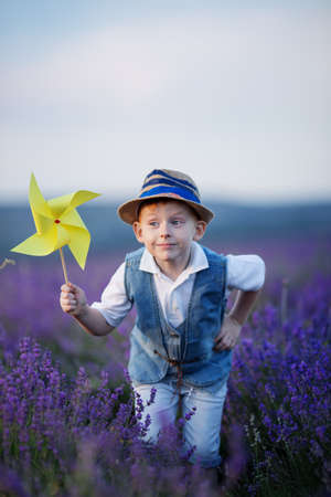 Happy fashion boy in lavender summer field with yellow windmill in hands at sunset.