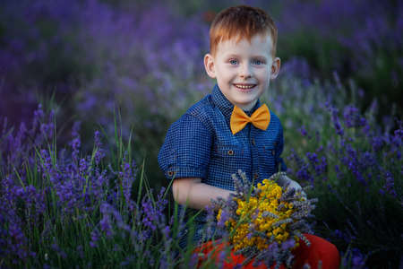 Happy fashion boy in lavender summer field with lavender bouquet in hands at sunset.