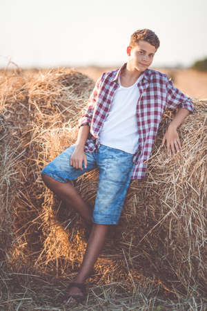 Pretty teen boy is wearing casual clothes near on stack of hay in the field