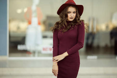 Fashion woman is wearing fashion autumn red clothes and hat infront of shop-window Stock Photo