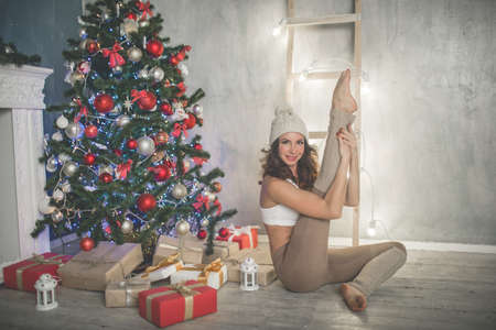 Beautiful flexible young woman is doing sports near decorated christmas tree, sports and holiday concept