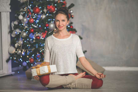 Beautiful flexible smiling woman is doing stretching exercise near decorated fashion xmas tree at home, sports and holiday concept Stock Photo