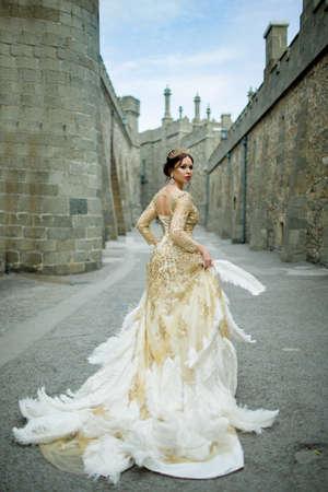 De mooie sexy vrouw draagt prinseskleding met veren in het magische kasteel Stockfoto