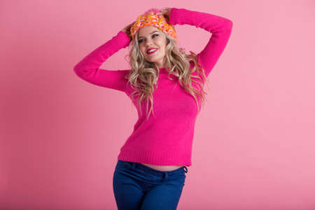 Blonde happy pregnant woman is wearing warm winter clothes hat and sweater isolated on pink background