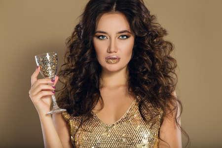 Portrait of beautiful girl with rhinestones on her lips is wearing golden dress, studio shoot