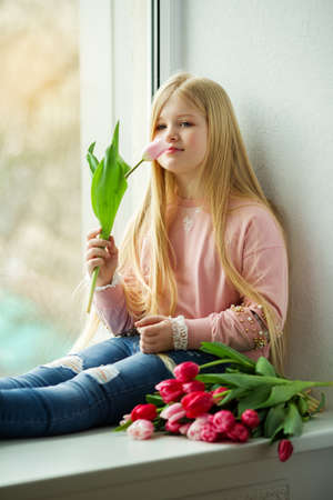 Pretty blonde girl with bouquet of tulip pink flowers. Easter concept