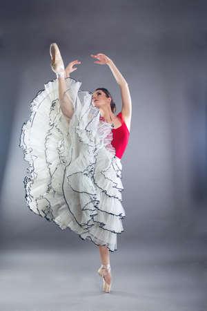 Hermosa mujer delgada bailarina de ballet en estudio aislado en gris Foto de archivo - 97894213